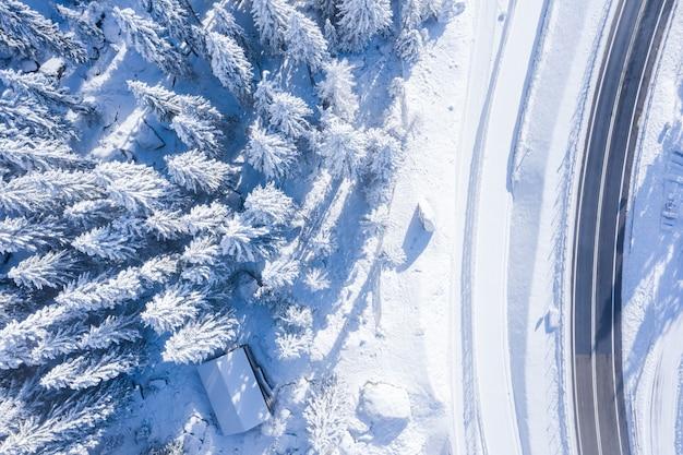 Luchtfoto van een bos met bomen bedekt met sneeuw en een tweebaansweg aan de zijkant