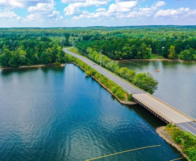 Luchtfoto van een brug, weg, bomen in de buurt van het meer met een bewolkte blauwe hemel