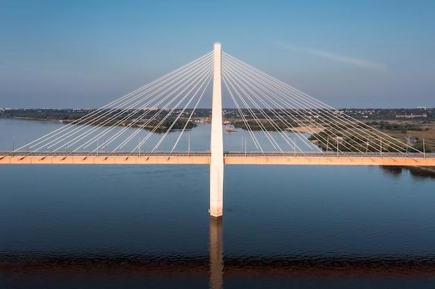 Luchtfoto van een centrale pijler van een tuibrug boven een rivier die in water reflecteert