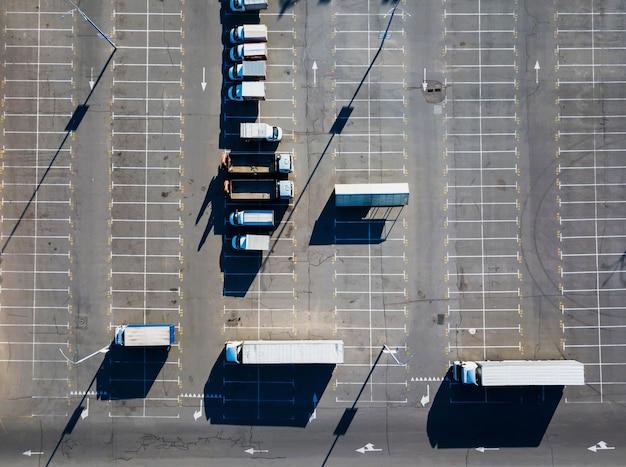 Luchtfoto van een drone met verschillende vrachtwagens op de parkeerplaats met weerspiegeling van de schaduwen van straatlantaarns op een zonnige dag. bovenaanzicht