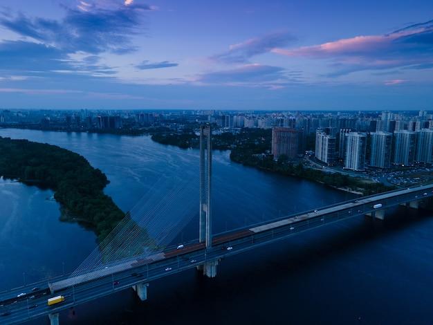 Luchtfoto van een drone op een tuibrug over een rivier in een grote stad in de avond