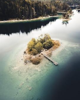 Luchtfoto van een eiland met bomen en een huis met een houten pier vlakbij de kust