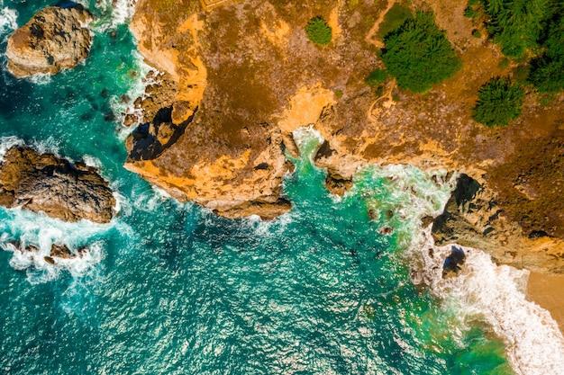 Luchtfoto van een golvende zee tegen de kliffen overdag