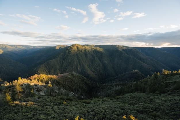 Luchtfoto van een groen bergachtig landschap tijdens zonsopgang