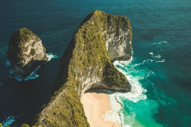 Luchtfoto van een groene, overdekte klif omringd door het overweldigende oceaan-nusa penida-eiland indonesië