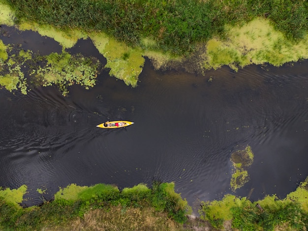 Luchtfoto van een groep kajaks die op een zomerdag op een bosrivier reizen