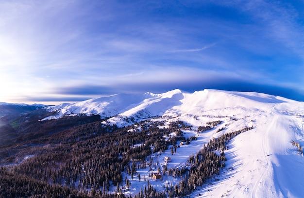 Luchtfoto van een helder mooi panorama van een skihelling met sparren en sneeuw op een zonnige ijzige dag met rokerige wolken