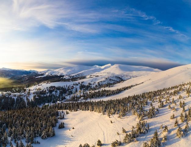 Luchtfoto van een helder mooi panorama van een skihelling met sparren en sneeuw op een zonnige ijzige dag