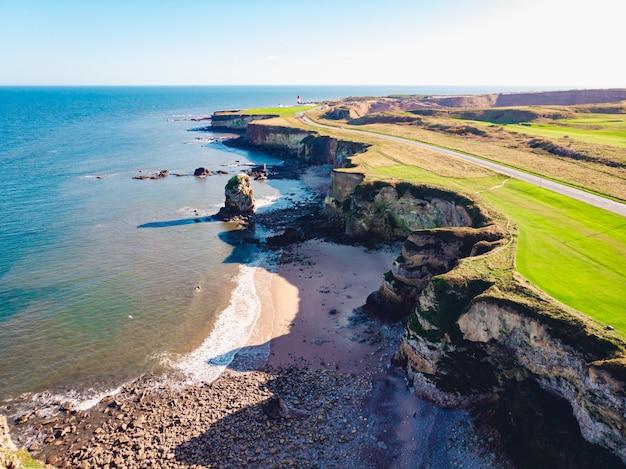 Luchtfoto van een helderblauwe zee en een met gras begroeide kust