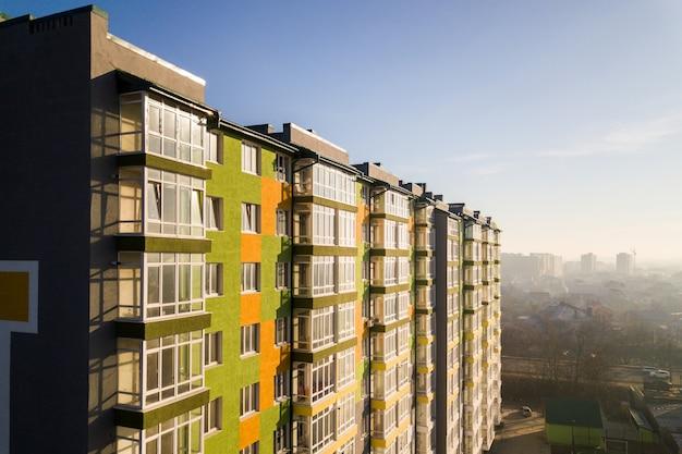 Luchtfoto van een hoog woonappartementengebouw met veel ramen en balkons.