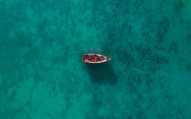 Luchtfoto van een houten boot in het water, schip en boot in een prachtige turkooizen oceaan