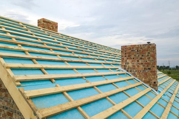 Luchtfoto van een houten dakframe van bakstenen huis in aanbouw.