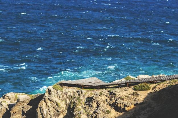 Luchtfoto van een houten pad op de rotsen boven de oceaan