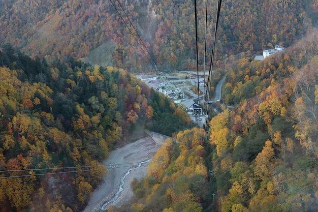 Luchtfoto van een kabelbaan van kurodake ropeway vliegen over kleurrijke herfstbossen