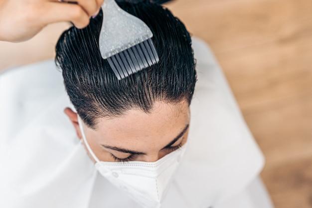 Luchtfoto van een kapper die haarverf met een borstel aanbrengt op het haar van een man met masker in een salon
