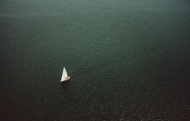 Luchtfoto van een kleine boot zeilen in de brede prachtige oceaan