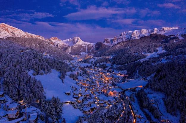 Luchtfoto van een kleine, heldere stad tussen besneeuwde bergen tijdens de avond
