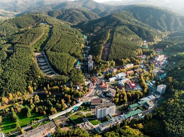 Luchtfoto van een kleine stad op het grondgebied van de altai. bovenaanzicht van de badplaats belokurikha. vogelvlucht van de huizen tussen de bossen op de hellingen van de bergen.