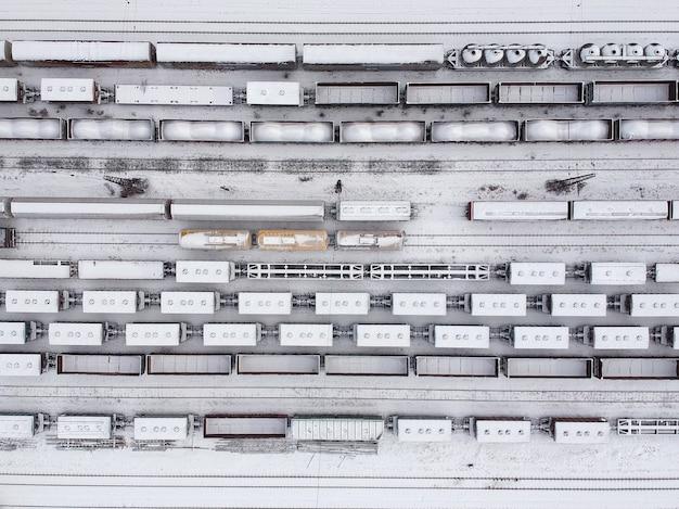 Luchtfoto van een lading treinen in witter. goederentreinen bedekt met sneeuw op het station. zware industrie. geen mensen.