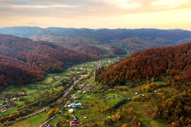 Luchtfoto van een landelijk dorp met kleine huizen tussen herfstbergheuvels bedekt met gele en groene pijnbomen.