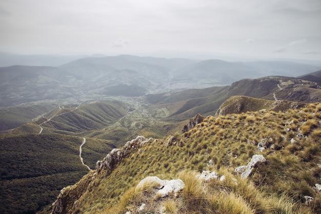 Luchtfoto van een landelijke weg die door de bomen en bergen loopt