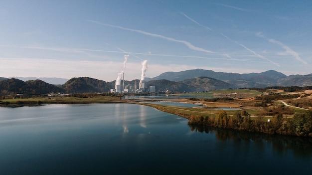 Luchtfoto van een landschap omringd door bergen en meren met een industriële ramp