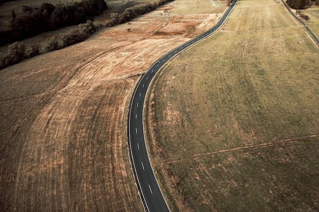 Luchtfoto van een lange asfaltweg omgeven door velden