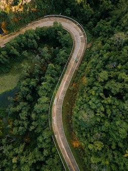 Luchtfoto van een lange weg omringd door bomen en velden