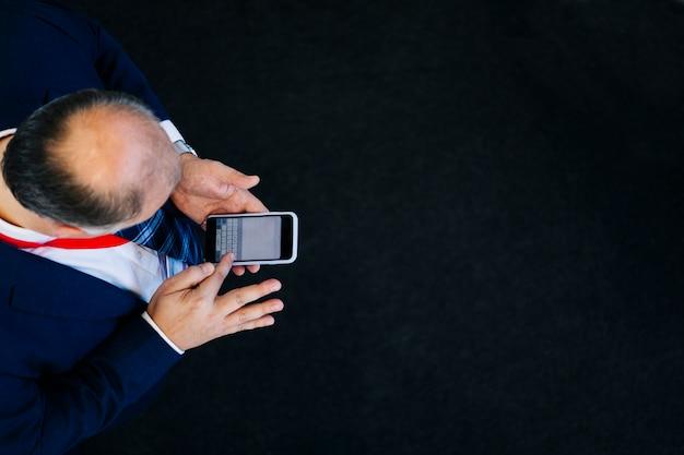 Luchtfoto van een man met behulp van een mobiele telefoon op een zwarte vloer