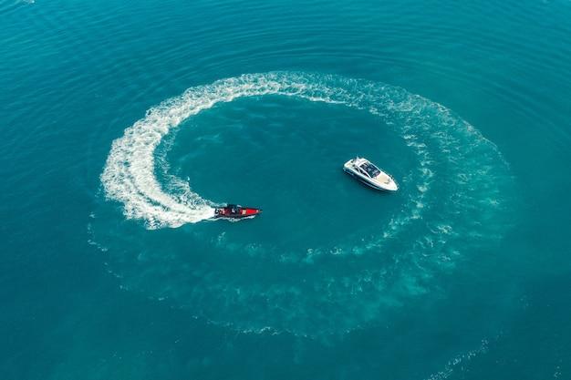 Luchtfoto van een motorboot die vaart op de azuurblauwe wateren van de andamanse zee rond het jacht