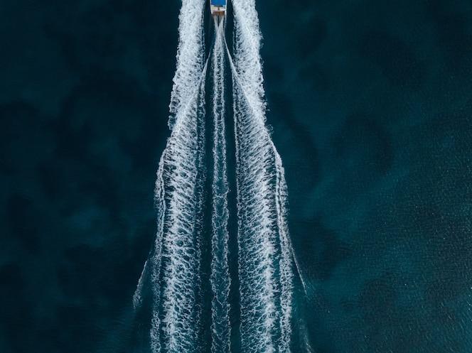 Luchtfoto van een motorboot die vooruit in het midden van de oceaan vaart