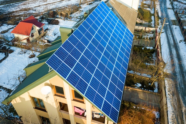 Luchtfoto van een nieuw modern huis met twee verdiepingen en een blauw glanzend fotovoltaïsch zonnepaneelsysteem op het dak. hernieuwbaar ecologisch groene energieproductieconcept.
