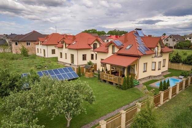 Luchtfoto van een nieuwe autonome woning met zonnepanelen en waterverwarmingsradiatoren op het dak
