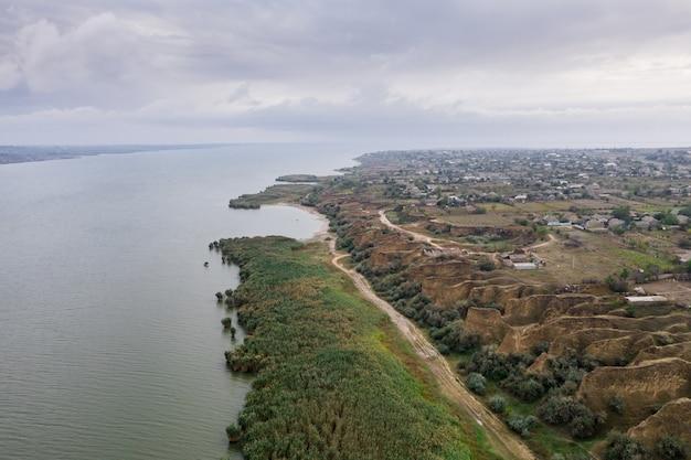 Luchtfoto van een pad langs een enorm meer met prachtige zandduinen en groene kust