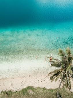 Luchtfoto van een persoon die in de kristalheldere oceaan zwemt