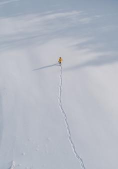 Luchtfoto van een persoon die loopt in een veld bedekt met sneeuw