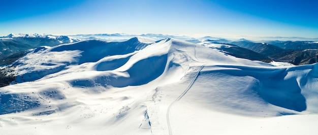 Luchtfoto van een prachtig besneeuwd skigebied met besneeuwde heuvels in de bergen en toeristische site op een zonnige heldere ochtend