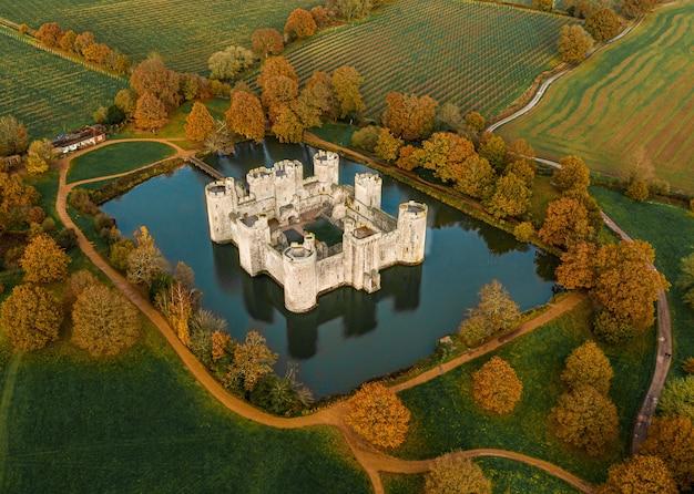 Luchtfoto van een prachtig oud kasteel midden in een meer, omringd door bomen en boerderijen