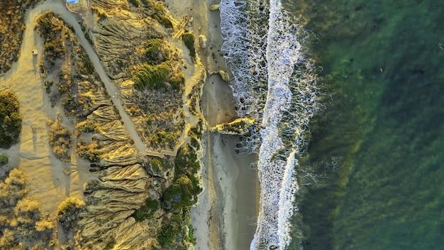 Luchtfoto van een prachtig strand met zand en groene bomen