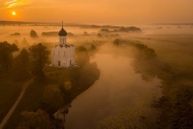 Luchtfoto van een russisch-orthodoxe kerk boven een mistig veld verlicht door de rijzende zon met een vijver in de buurt van de kerk en een rivier op de achtergrond