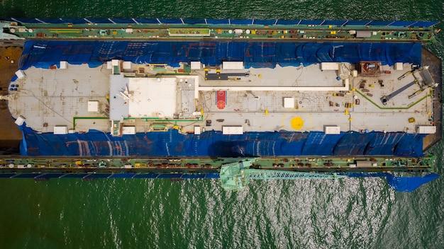 Luchtfoto van een scheepswerf die een groot schip in thailand herstelt.