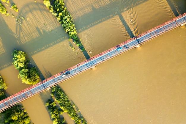Luchtfoto van een smalle wegbrug die zich uitstrekt over modderige brede rivier in groen landelijk gebied.