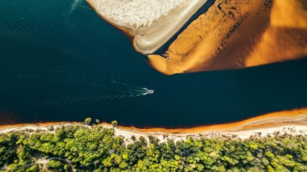 Luchtfoto van een speedboot die langs de rivier vaart aan de kust van goudkleurig zand