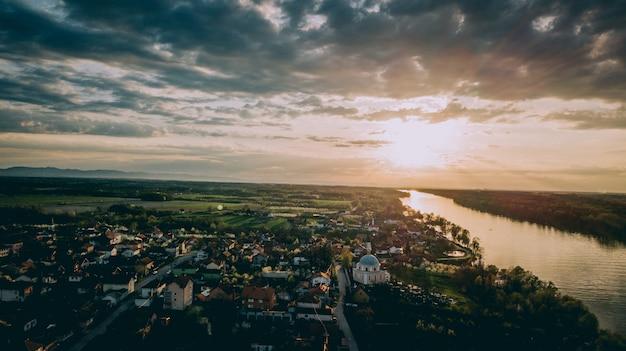 Luchtfoto van een stad in de buurt van een rivier en grasvelden onder een bewolkte hemel