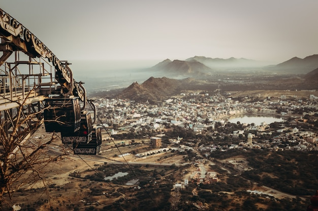 Luchtfoto van een stad in een vallei met een meer en rotsachtige bergen en een roestige verlaten kabelbaan