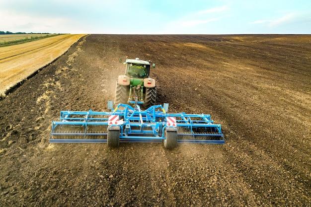 Luchtfoto van een tractor die een zwart landbouwveld ploegt na het oogsten in de late herfst.
