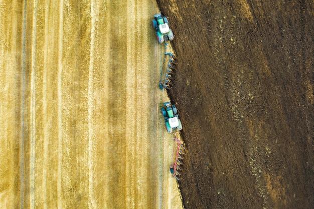 Luchtfoto van een tractor ploegen zwarte landbouw boerderij veld in de late herfst.
