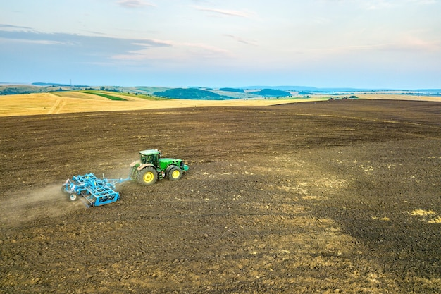 Luchtfoto van een trekker zwarte landbouw boerderij veld ploegen na de oogst in de late herfst