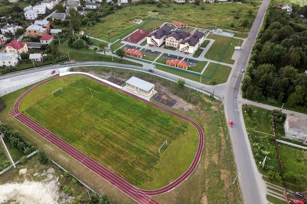 Luchtfoto van een voetbalveld op een stadion bedekt met groen gras in landelijke stad.