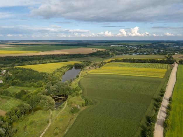 Luchtfoto van een vogelvlucht naar een landelijk landschap met onverharde weg, landbouwvelden van geplante gewassen in de zomer bij zonsondergang. uitzicht vanaf vliegende drone.